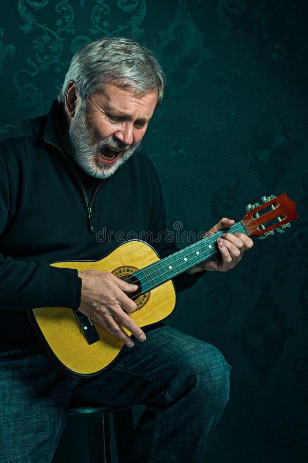 Pracowniany portret starszy mężczyzna z gitarą zdjęcie royalty free