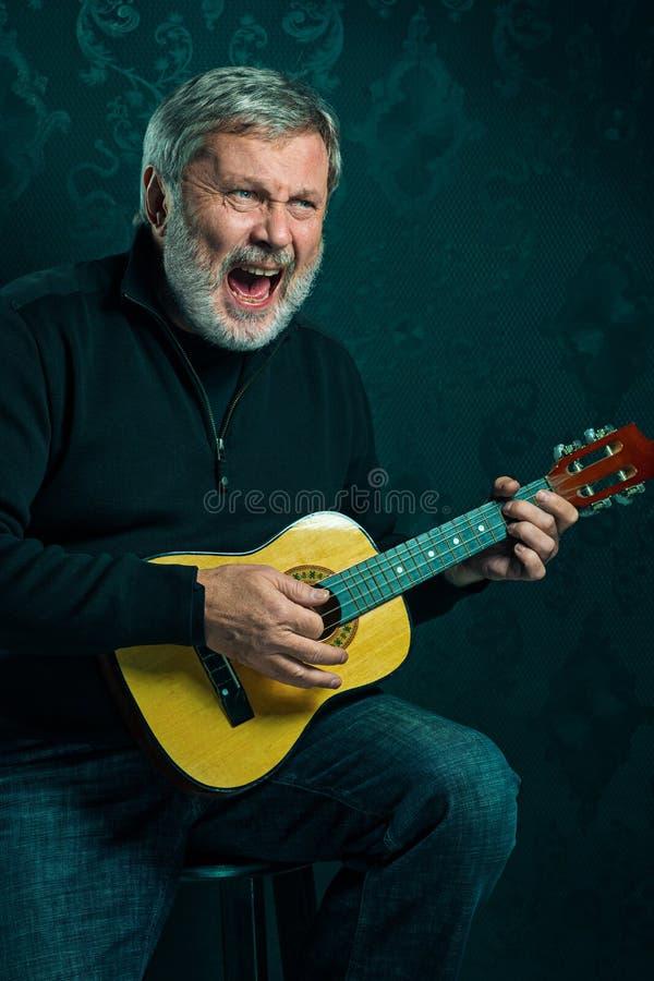 Pracowniany portret starszy mężczyzna z gitarą obrazy stock