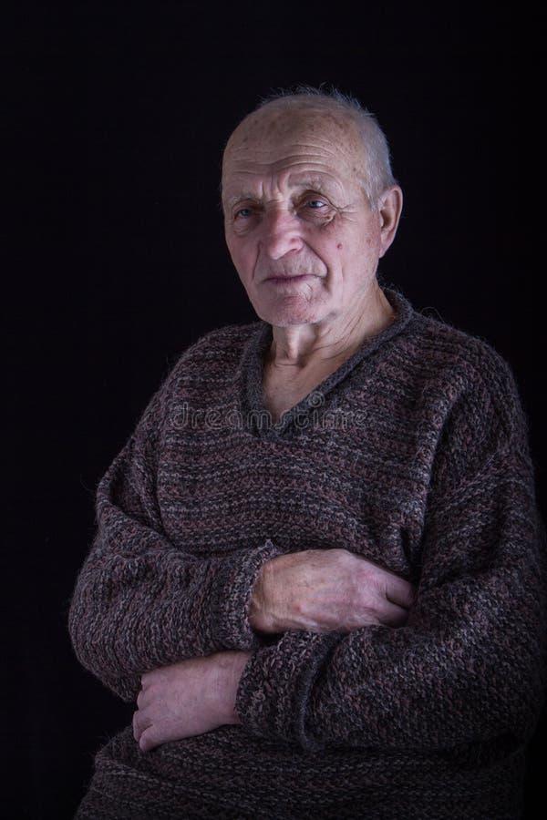 Pracowniany portret stary cz?owiek w brutalnym pulowerze na czarnym tle, selekcyjna ostro?? zdjęcie stock