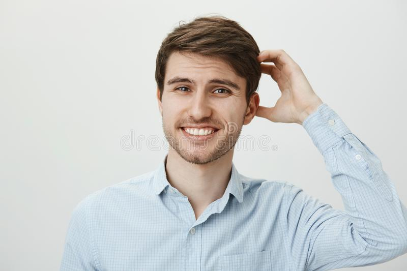 Pracowniany portret wahać się intrygującego atrakcyjnego europejskiego faceta z broda chrobota głową i ono uśmiecha się z nerwowy fotografia stock