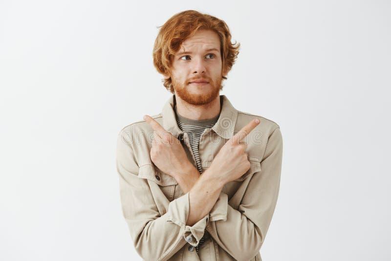 Pracowniany sht zmieszanej ślicznej rudzielec samiec europejski model z chorą brodą w kurtce nad koszulką wskazuje z krzyżujący zdjęcie stock