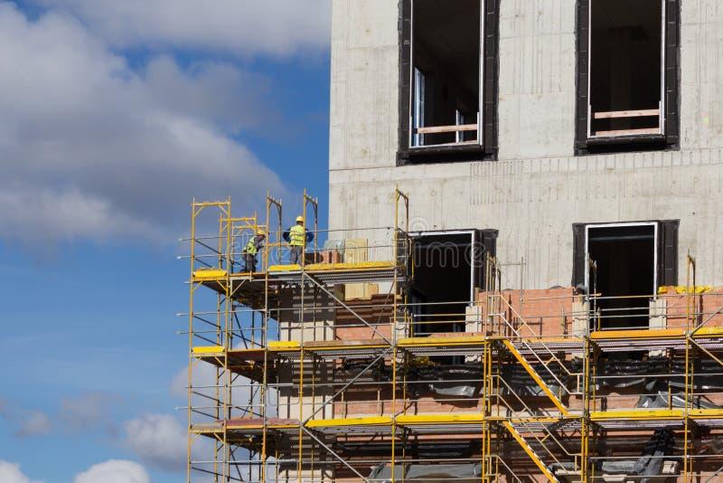 Pracownicy budowlani na rusztowaniu - budynek fasady constructi fotografia stock