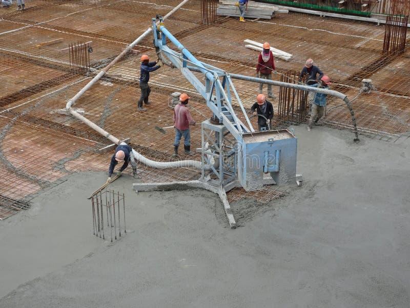 Pracownicy budowlani nalewa mokrego betonowego używa betonowego pająka węża elastycznego fotografia stock