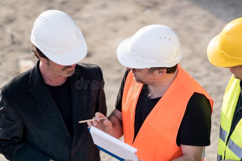 Pracownicy budowlani opowiada na budowie obraz stock