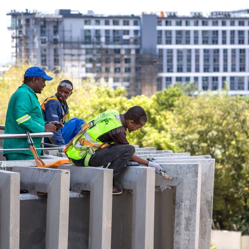 Pracownicy budowlani pracuje na budynek fasadzie zdjęcia stock