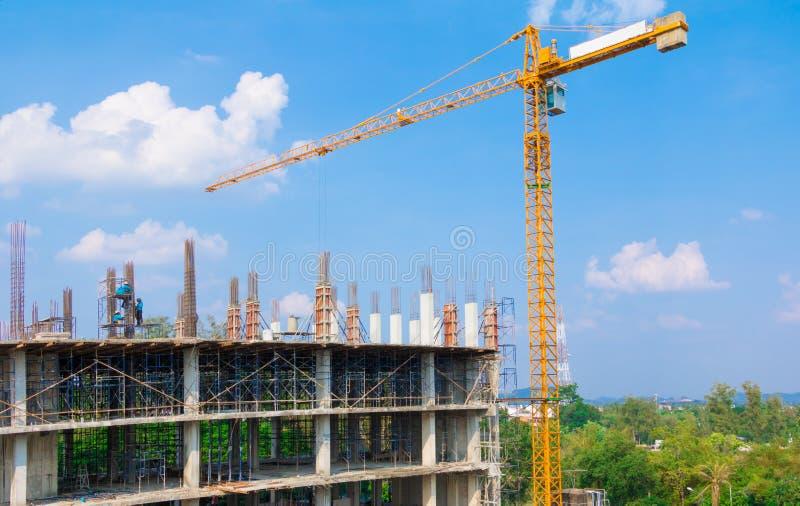 Pracownicy budowlani są usytuowanym przy laborer pracą plenerową która basztowego żurawia niebieskiego nieba tło z kopii sp i bud zdjęcia stock
