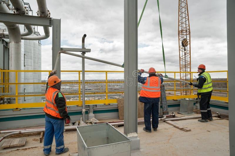 Pracownicy budowlani umieszcza drymbę podnoszącą żurawiem fotografia stock