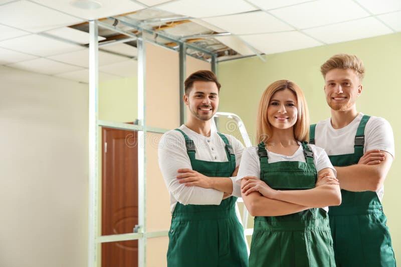 Pracownicy budowlani w mundurach Domowa remontowa us?uga fotografia royalty free