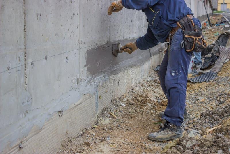 Pracownicy budowlani z muśnięcie stosować wodną izolacją fotografia royalty free