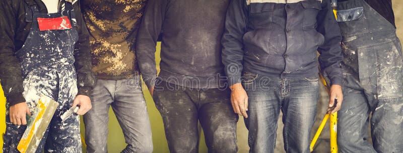 Pracownicy, budowniczowie i brygadier są gdy gang z brudnym mundurem zostaje w mieszkaniu przemodelowywa który jest w budowie, zdjęcia stock
