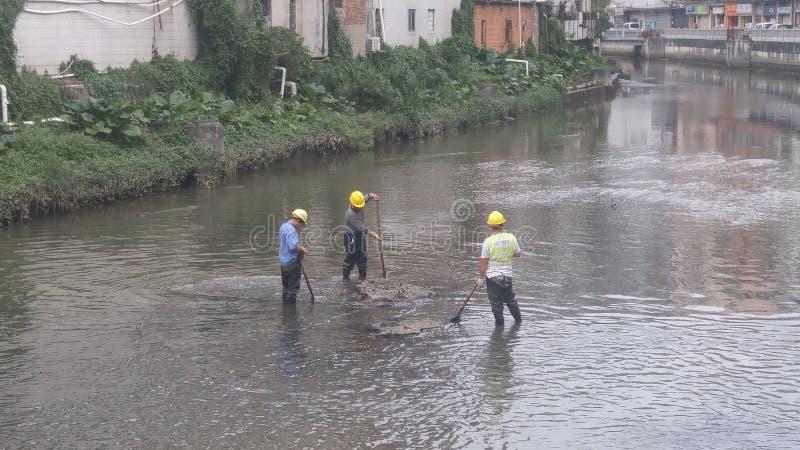 Pracownicy czyścą up namuł w xixiang rzece w Shenzhen, Chiny obraz royalty free