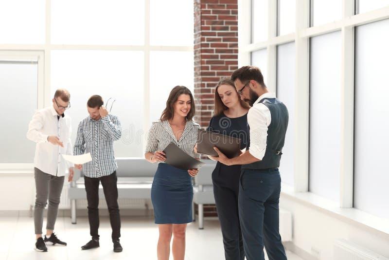 Pracownicy dyskutuje biznesowych dokumenty w biuro lobby fotografia royalty free