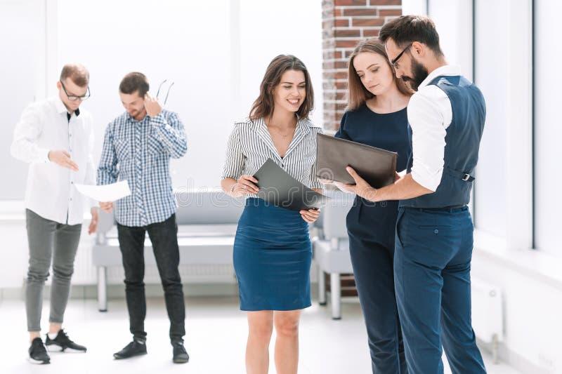 Pracownicy dyskutuje biznesowych dokumenty w biuro lobby obraz stock