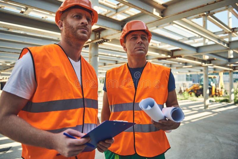 Pracownicy firma budowlana przeglądają przedmiot zdjęcia stock