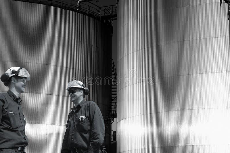 Pracownicy i przemysłowi paliwowi zbiorniki przy zmierzchem zdjęcia stock