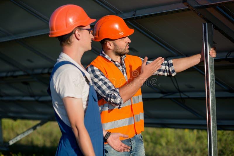 Pracownicy instaluje photovoltaic panel przy energii słonecznej stacją fotografia royalty free