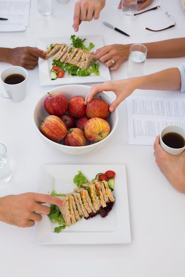 Pracownicy je zdrowego lunch podczas spotkania obraz stock