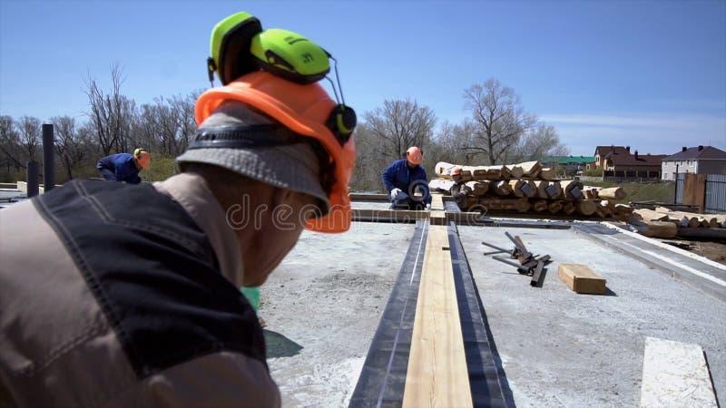 Pracownicy mierzyć drewniane deski przy budową klamerka Budowniczowie robią pomiarom deski dla budowy fotografia royalty free