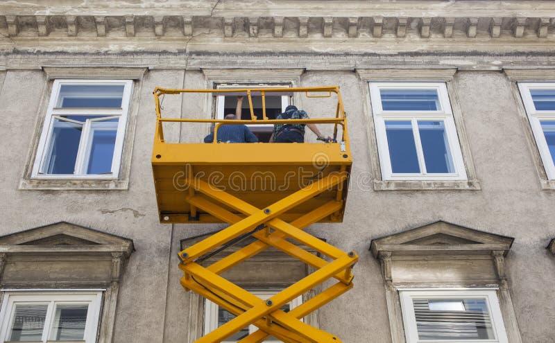 Pracownicy na czereśniowym zbieraczu odczyszczają fasadę budynek zdjęcie royalty free