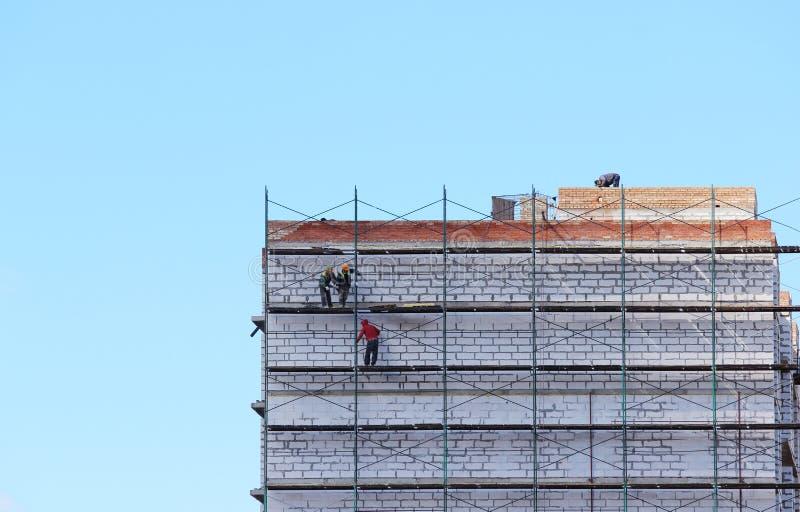 Pracownicy na rusztowaniu budują opowieść dom od bloków i cegieł zdjęcia royalty free