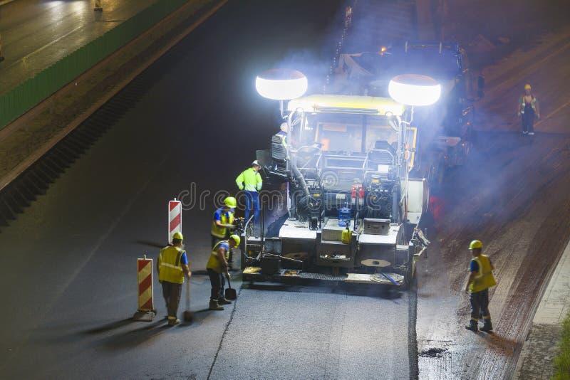 Pracownicy napraw asfaltu ulicznego w porze nocnej obraz stock
