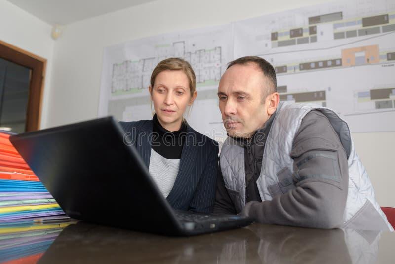 Pracownicy patrzeje laptop w biurze zdjęcie royalty free