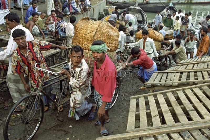 Pracownicy rozładowywają łodzie w ruchliwie portowym Dhaka fotografia stock