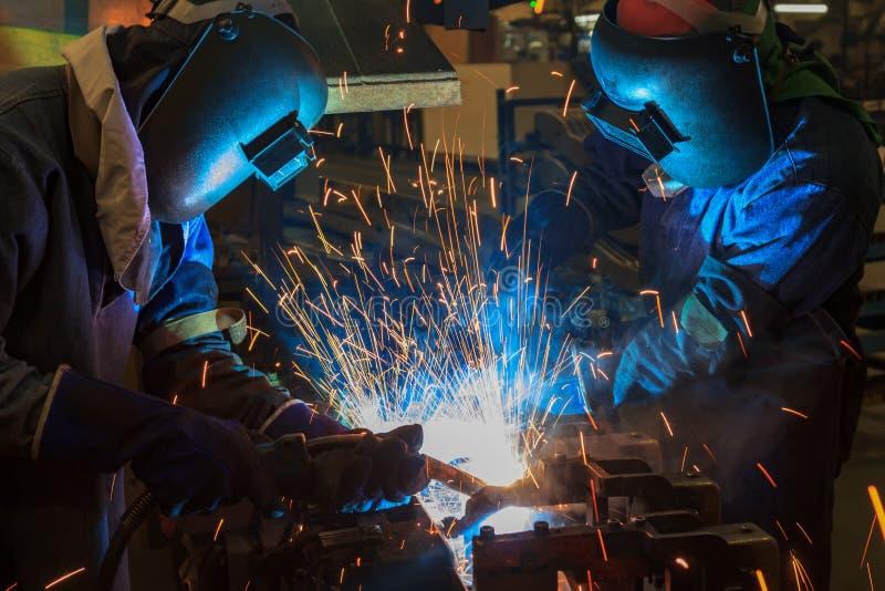 Pracownicy spawają zgromadzenie samochodowe części w automobilowej przemysłowej fabryce obrazy stock