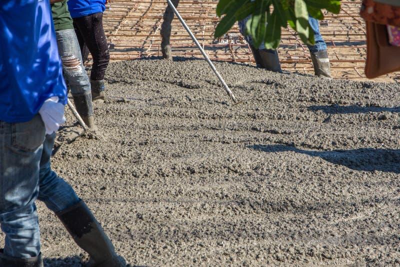 Pracownicy używa drewnianą szpachelkę dla cementu po Nalewać mieszającego beton obraz stock