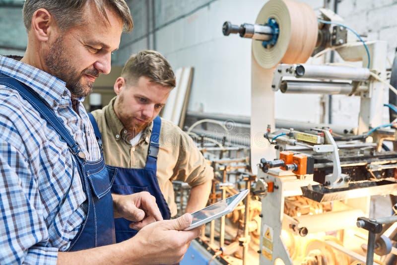 Pracownicy Używa Nowożytną maszynę przy fabryką zdjęcia stock