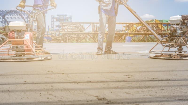 Pracownicy używają betonowe polerownicze maszyny dla cementu po tym jak Nalewający mieszającego beton zdjęcie stock