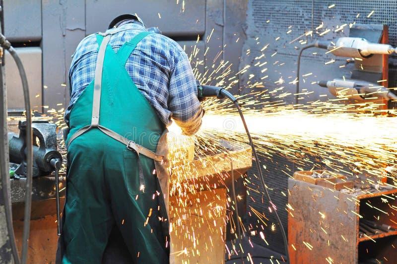 Pracownicy w formierni mleją kasting z szlifierską maszyną - On fotografia stock