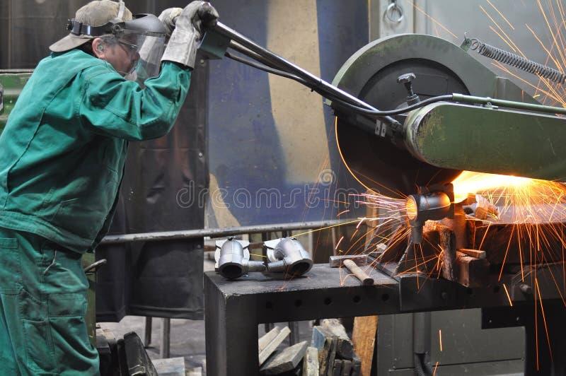 Pracownicy w formierni mleją kasting z szlifierską maszyną - On obraz stock
