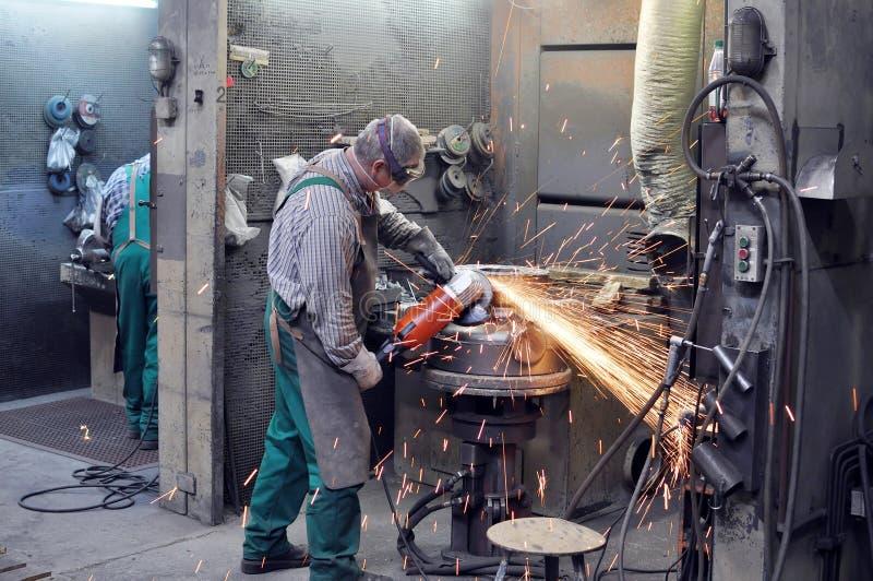 Pracownicy w formierni mleją kasting z szlifierską maszyną - On zdjęcie royalty free