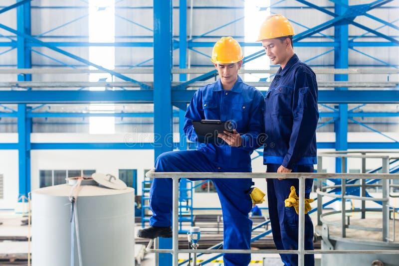 Pracownicy w wielkiego metalu warsztatowej sprawdza pracie zdjęcie royalty free