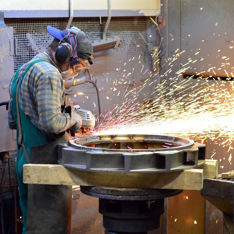 Pracownicy w zbawczej odzieży sanding kasting w przemysłowej firmie zdjęcia royalty free