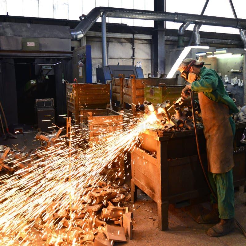 Pracownicy w zbawczej odzieży sanding kasting w przemysłowej firmie obraz stock