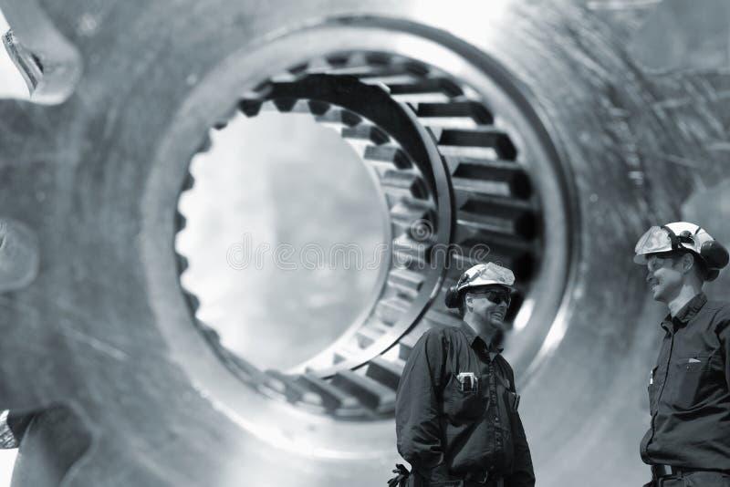 Pracownicy z gigantycznymi przekładniami i cogwheels axles obrazy stock