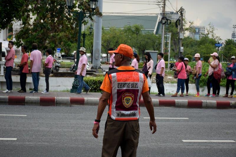 Pracowników ochronych udostępnienia Dla wiele ludzi chodzić w linii na footpath Wzdłuż Ratchadamnoen drogi, Bangkok, Tajlandia zdjęcie royalty free
