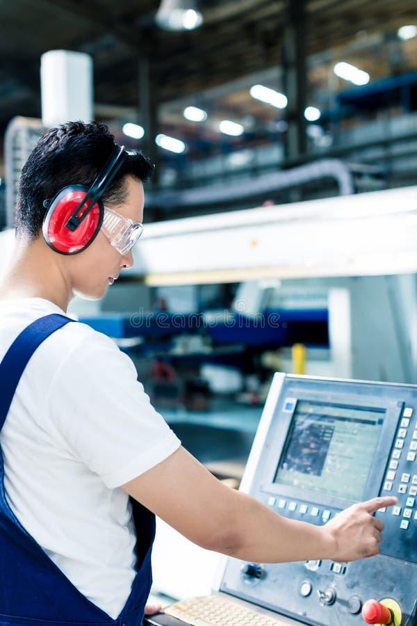 Pracowników wchodzić do dane w CNC maszynie przy fabryką obraz stock