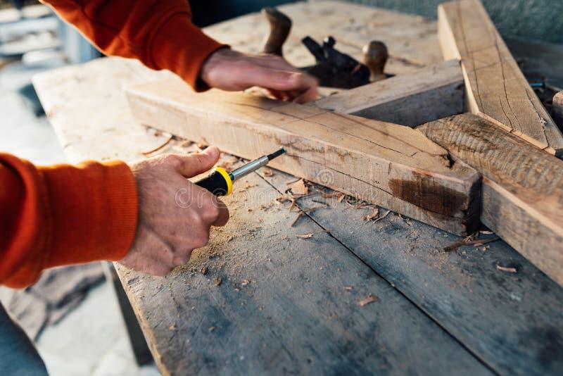 Pracownik śrubuje w górę drewnianego poręcza z śrubą z śrubokrętem na stole w trociny, zdjęcie royalty free