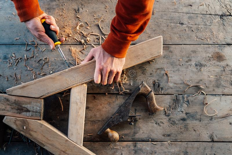 Pracownik śrubuje w górę drewnianego poręcza z śrubą z śrubokrętem na stole w trociny, obraz stock