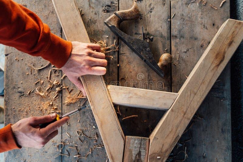 Pracownik śrubuje w górę drewnianego poręcza z śrubą z śrubokrętem na stole w trociny, obrazy royalty free