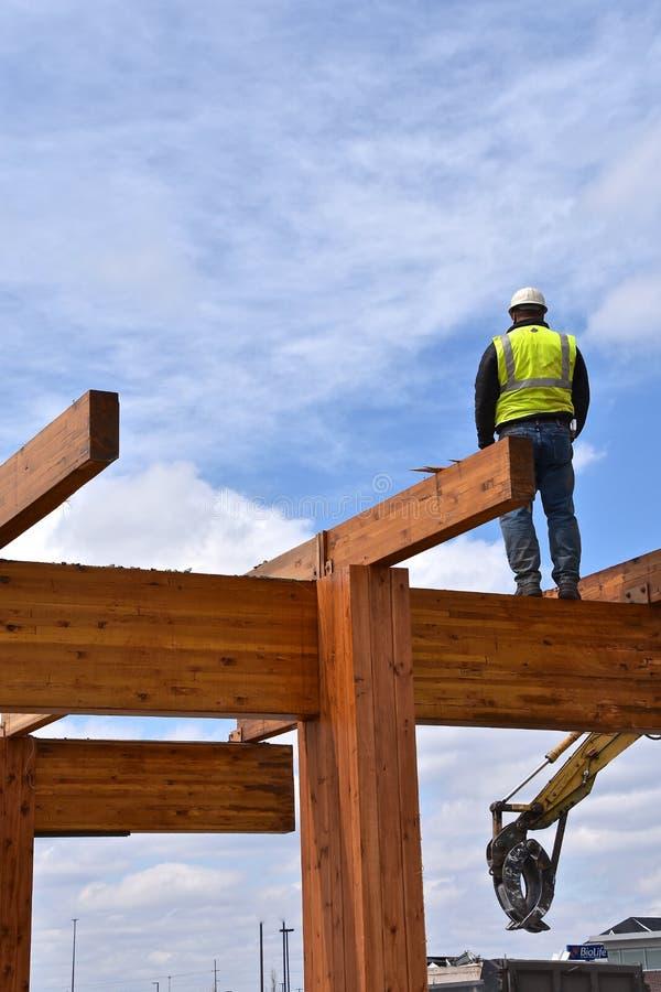 Pracownik budowlany chodzi na promieniach drewniany budynek fotografia royalty free