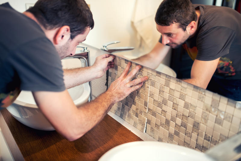 pracownik budowlany kłaść ceramiczne płytki, kaflarz umieszcza ceramiczną ściany płytkę w pozyci nad adhezyjnym fotografia stock