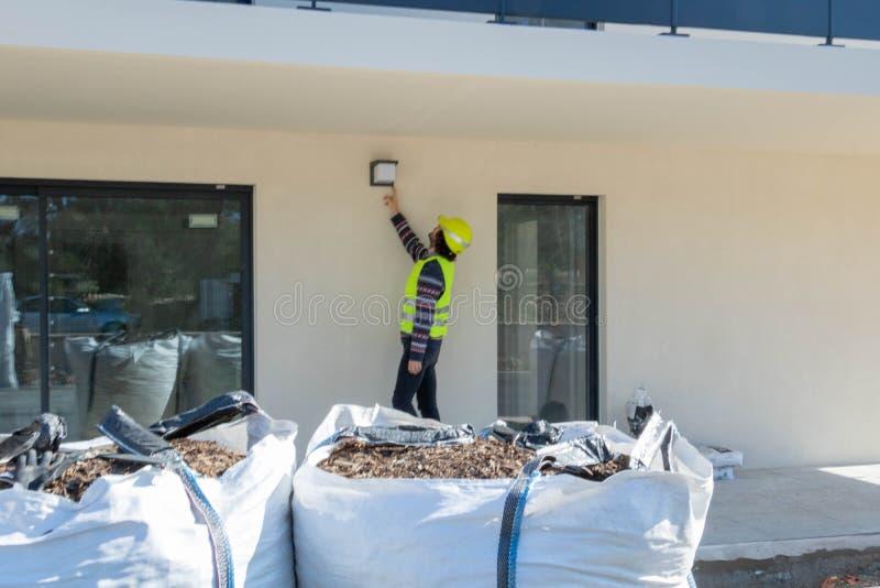 Pracownik budowlany, manewr pozuje elektrycznego oświetlenie na budynku w budowie obrazy stock