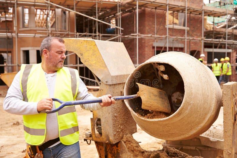 Pracownik Budowlany Miesza cement Na placu budowy obrazy royalty free