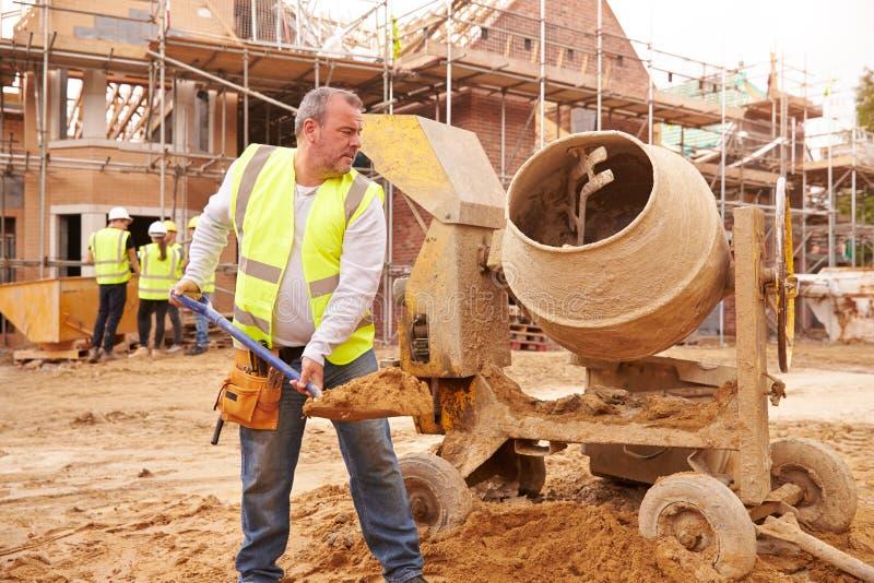 Pracownik Budowlany Miesza cement Na placu budowy zdjęcie stock
