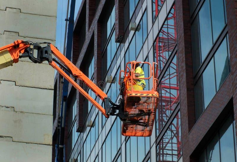 Pracownik budowlany na pomarańczowej podwyższonej platformie na wielkim nowożytnym placu budowy obraz stock