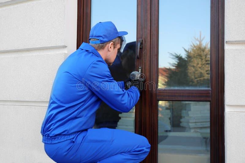 Pracownik budowlany naprawia szklanego drzwi zdjęcia stock